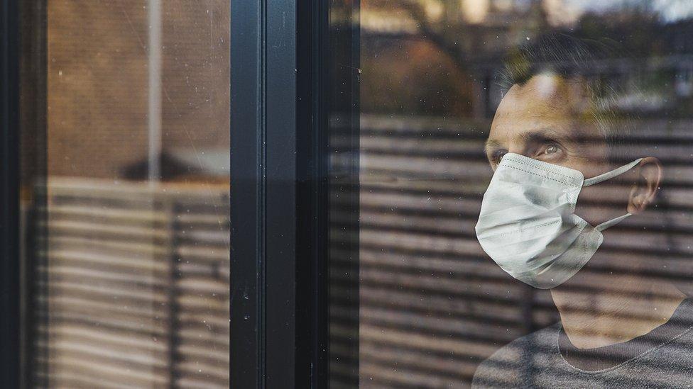 Hombre con mascarilla facial mirando a través de una ventana.