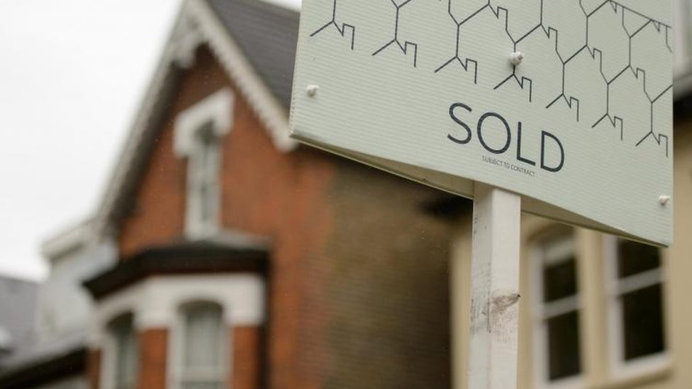 Sold sign next to house