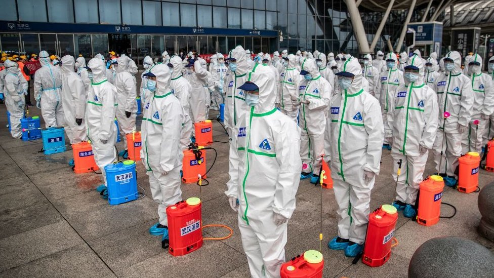 A squad of workers prepare to carry a disinfection operation at a Wuhan train station in March