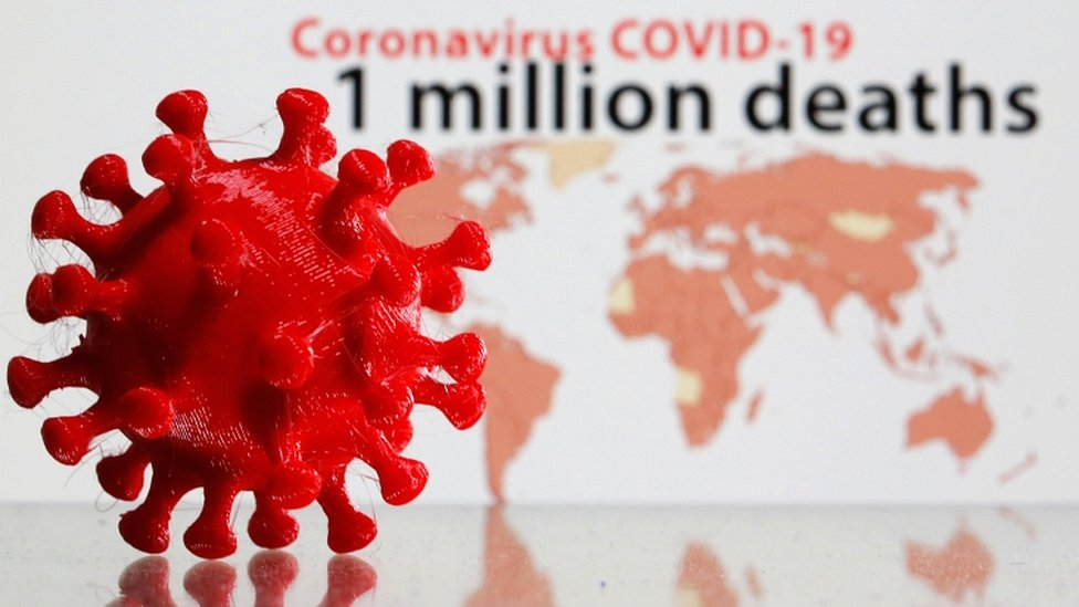 """A 3D printed coronavirus model is seen in front of the words """"Coronavirus COVID-19, one million deaths"""" on display in this illustration"""