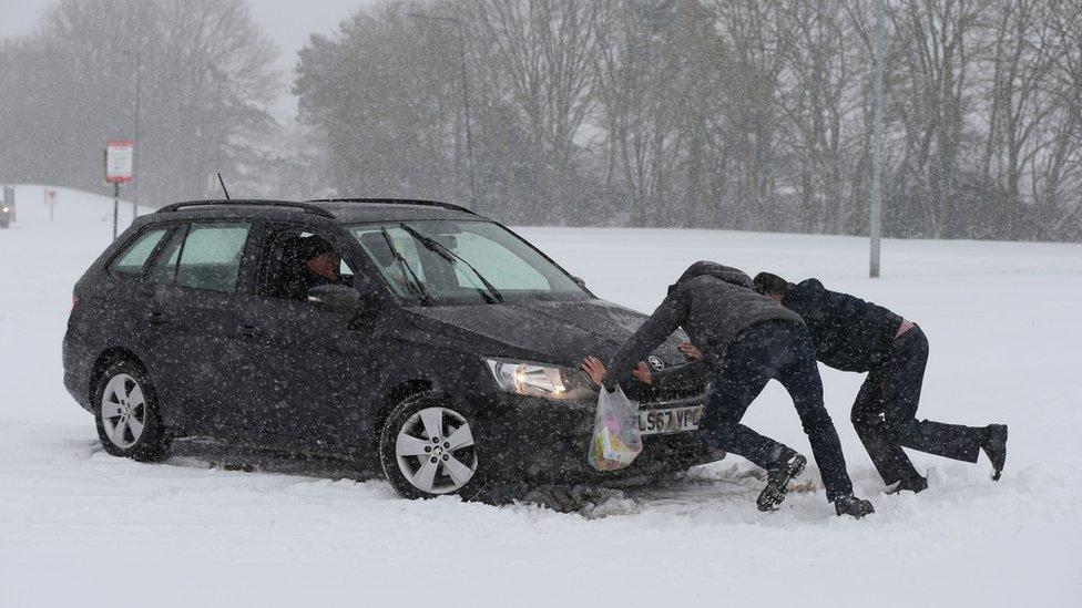سيارة عالقة في الثلوج ورجال يحاولون تحريكها.