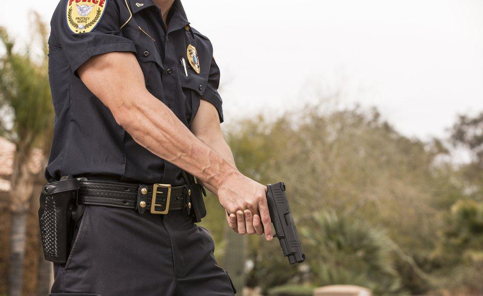 Policía sostiene una pistola.