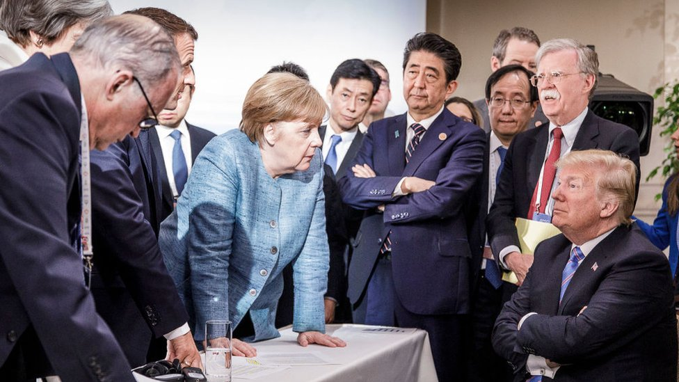 Merkel y otros líderes mundiales dialogan con Donald Trump en la cumbre del G7 en 2018.