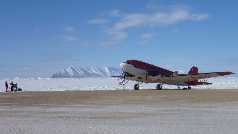 A red aeroplane stationary on a landing strip. Ice field and mountains visible in the background.