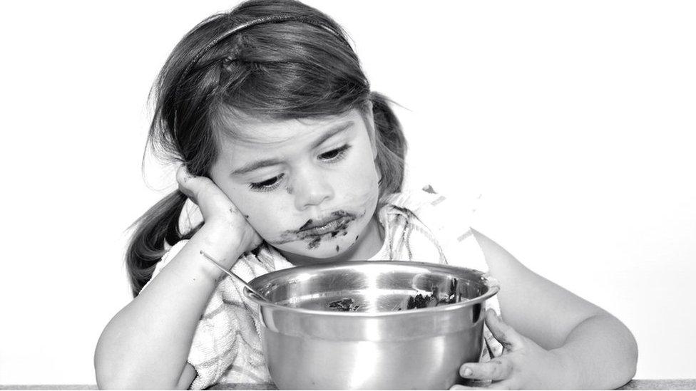 طفلة حزينة تأكل كعك
