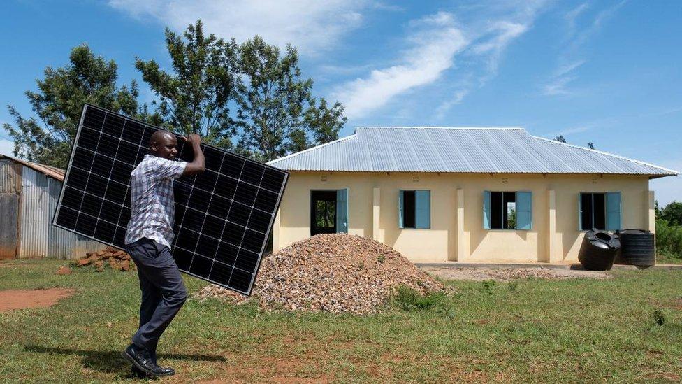 Hombre carga panel solar en Busia, Kenia.