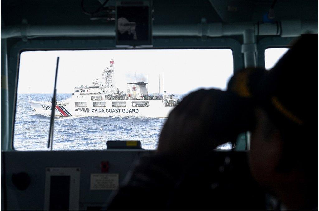 印尼軍艦上士兵用望遠鏡查看不遠處的中國海警船隻。