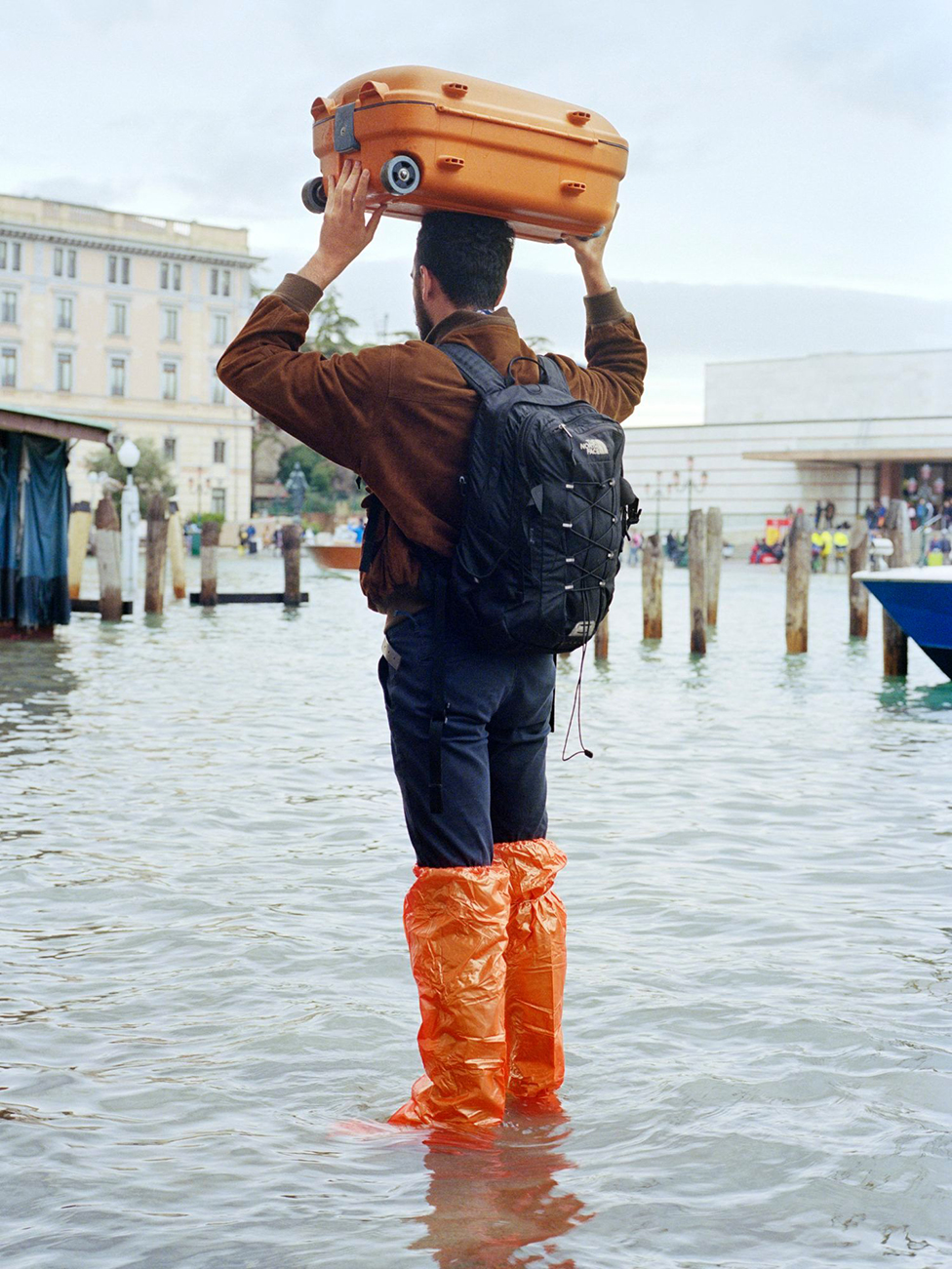 A man standing in high water in Venice, Italy.