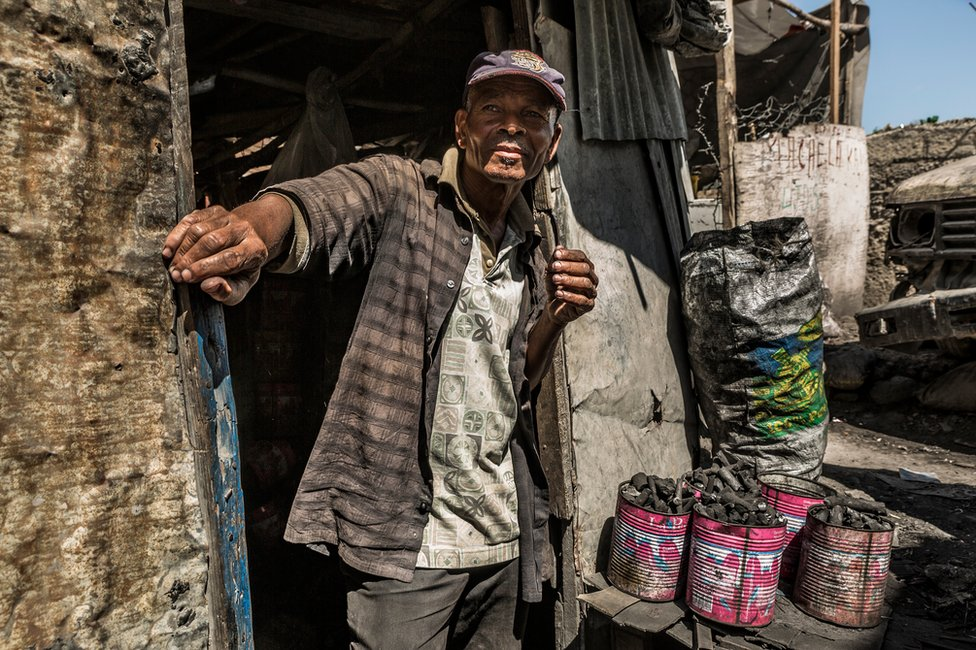 Loreu stands at the entrance to his charcoal shop