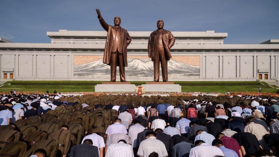 Gente haciendo reverencia ante las estatuas de Kim Jong-il y Kim Il-sung