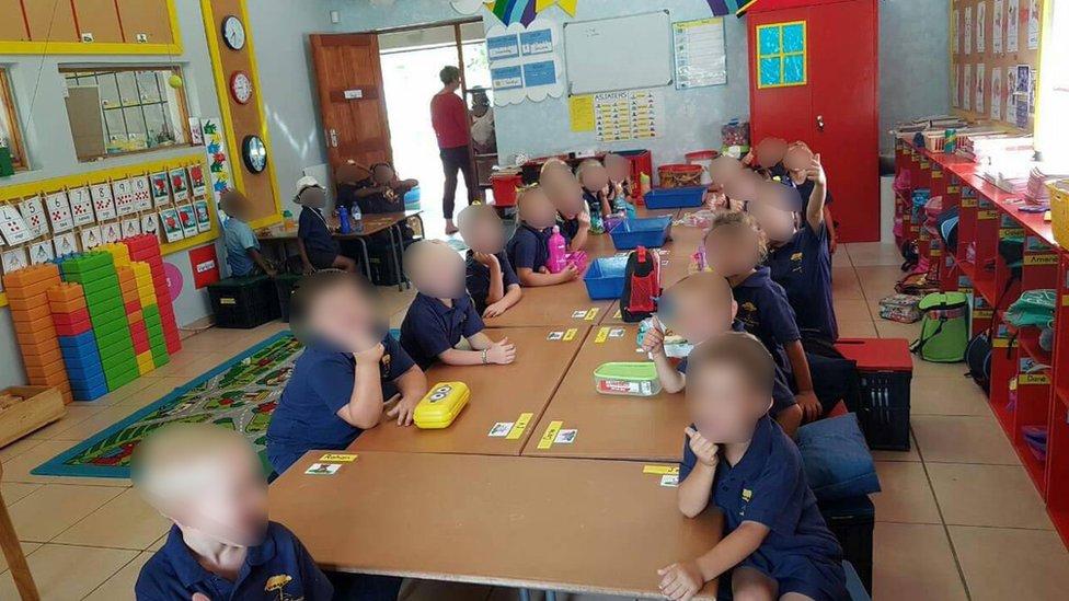 صورة لتلاميذ بيض البشرة يجلسون في منتصف الغرفة وبعض التلاميذ من أصحاب البشرة السمراء يجلسون بعيدا