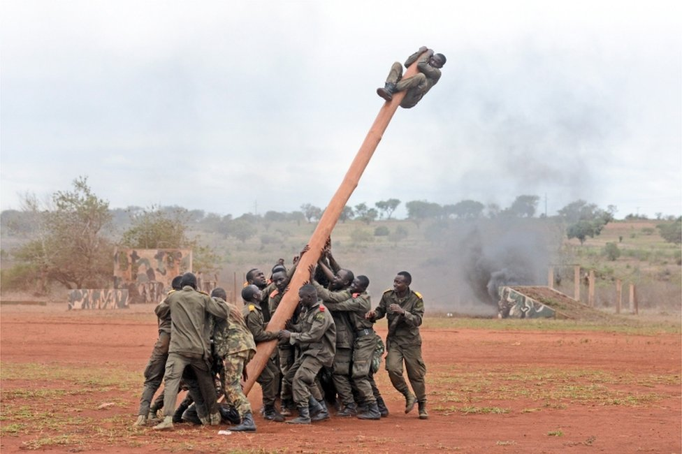 Soldiers hold on to one end of a large pole as their comrade clings to the other end in the air