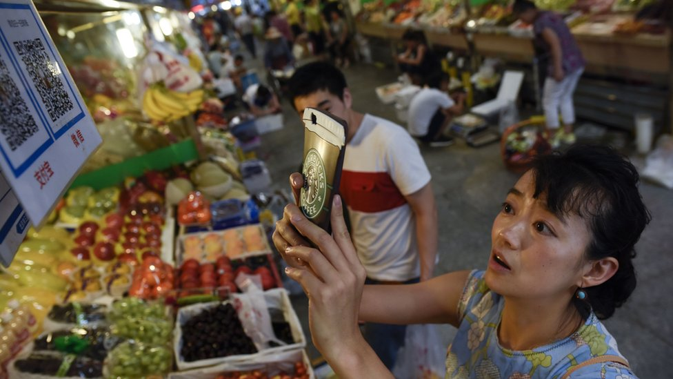 This photo taken in June 2017 shows a woman making purchases by scanning QR codes using her smartphone at a fruit stall in a market in Beijing