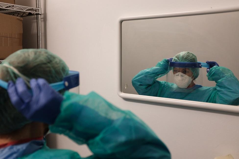 Una trabajadora de la salud usa máscara de protección. A