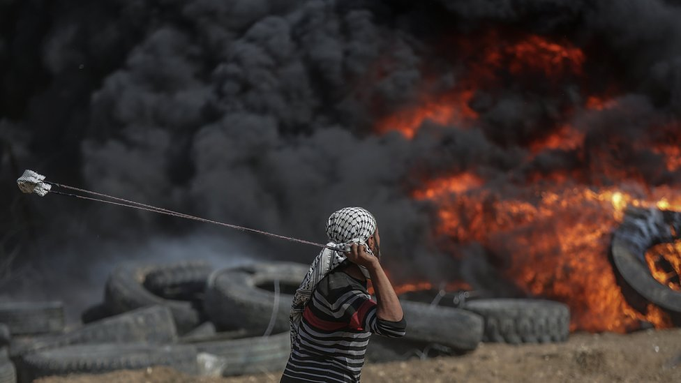 A Palestinian hurls a stone towards Israeli troops during a protest on the Gaza-Israel border on 27 April 2018