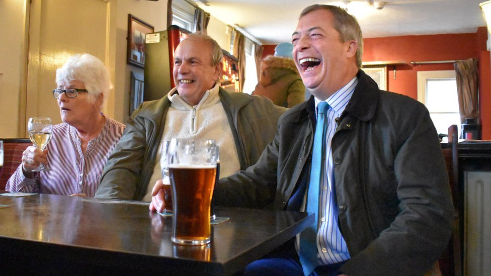 Brexit Party leader Nigel Farage (right) shares a joke with supporters after being bought a pint of bitter by a regular at the Wellington Inn in Eastwood, Nottinghamshire on 15 November
