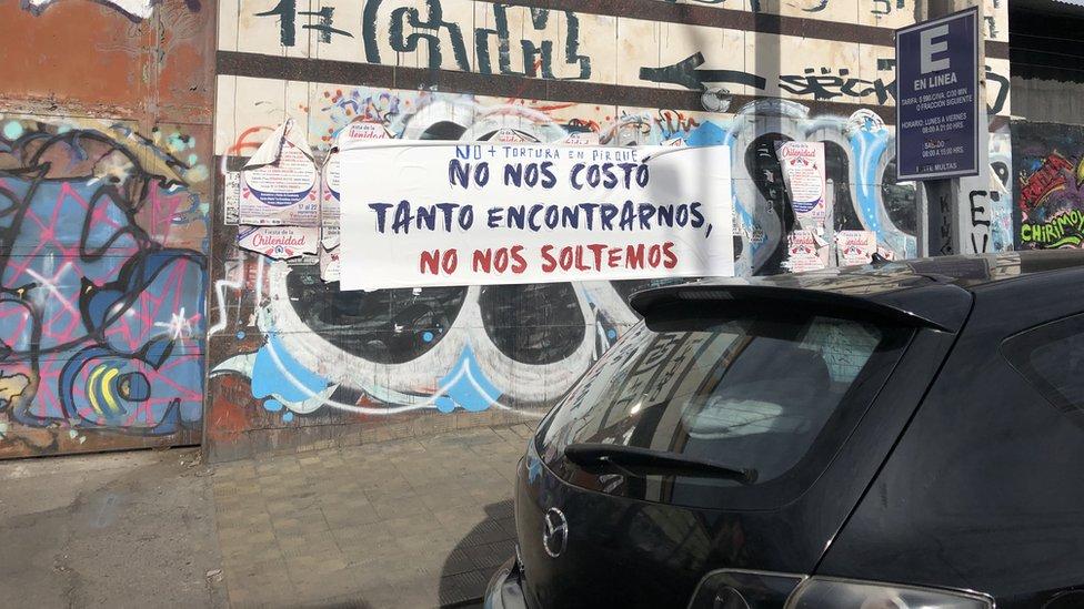 """""""No nos costó tanto encontrarnos, no nos soltemos"""", dice un cartel en la periferia de Santiago."""