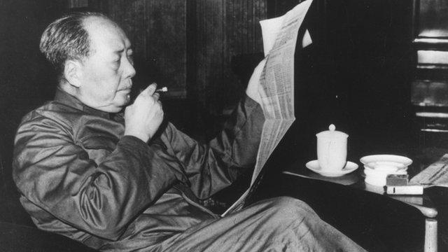 Chairman Mao smoking and reading a newspaper