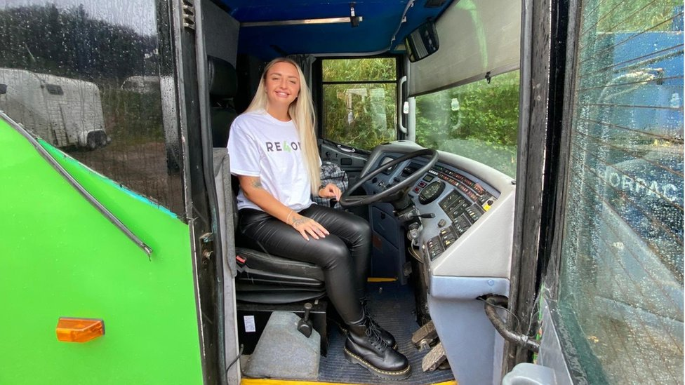RE4orm volunteer sitting in the driver's seat of the bus