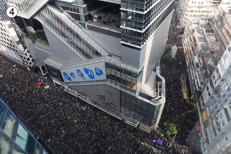 This shot from a building rooftop shows a converging V-shaped junction at the corner of a building - and huge crowds stretching off in either direction, even off the main route