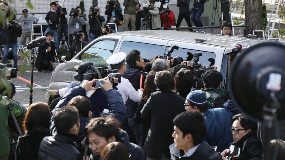 Fotógrafos rodean una camioneta de la policía que transporta a Takahiro Shiraishi en 2017.