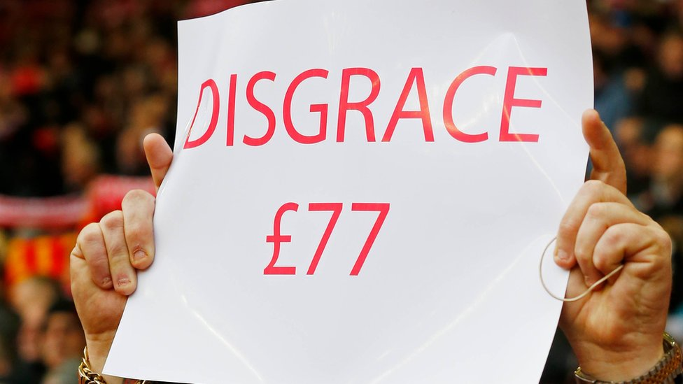 A Liverpool fan holds a banner protesting against a rise in ticket prices at Anfield in Liverpool, northwest England, on February 6, 2016.