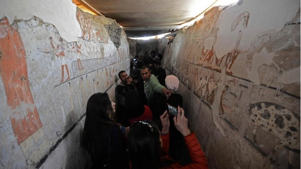Egyptians look at well-preserved and rare wall paintings inside the tomb of an Old Kingdom priestess in Saqqara, on the Giza plateau on the southern outskirts of Cairo, that was unveiled on 3 February 2018,