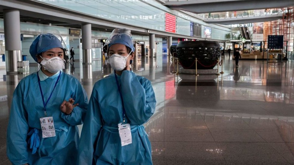 Security workers wearing protective gear as a preventive measure against the COVID-19 coronavirus walk through a nearly empty arrivals area at Beijing Capital Airport in Beijing on March 16, 2020