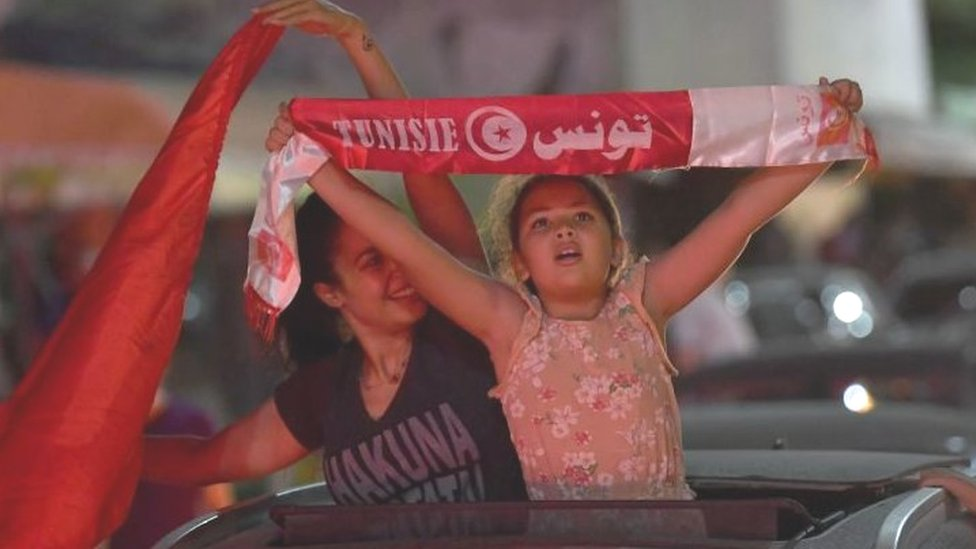 A little girl holds a scar with the Tunisian flag during a protest in Tunis