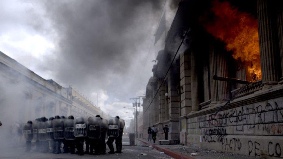Parte de la sede del Congreso de Guatemala en llamas con policías antimotines en frente