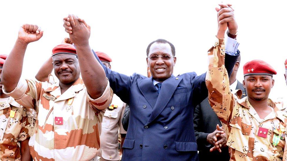 رئيس تشاد إدريس ديبي إيتنو (وسط) يمسك بيد جنرال من الكتيبة التشادية في مالي عمر بيكيمو (يسار) والرائد الثاني ونجله محمد إدريس ديبي إتنو (يمين) خلال حفل ترحيب ، في 13 مايو/أيار 2013 ، في نجامينا.