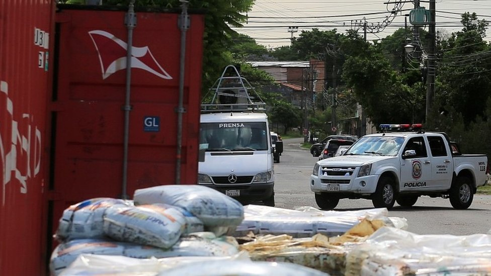A police vehicle is seen near a container where the authorities found decomposed bodies inside a fertiliser shipment