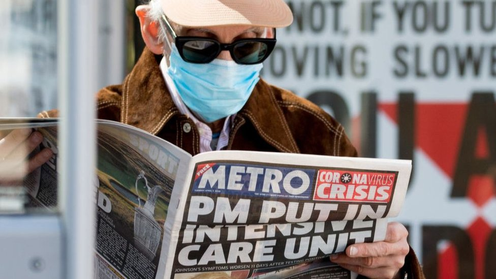 Un hombre con tapaboca lee un diario en Reino Unido
