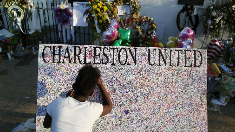 A girl writes on a poster for Charleston shooting victims