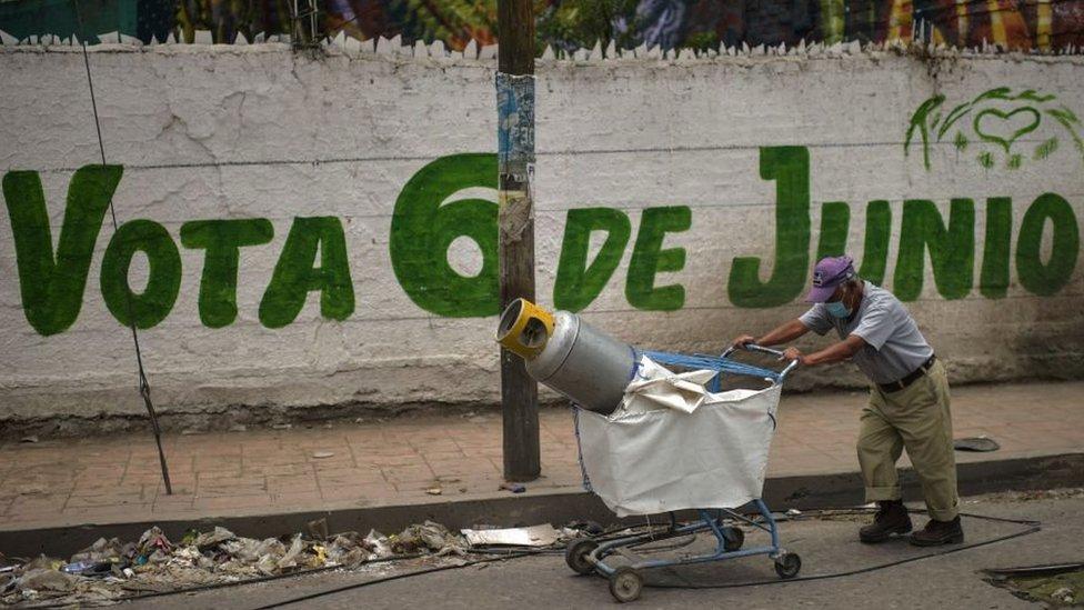 Hombre pasa frente a un cartel animando a votar en las elecciones de Mexico.