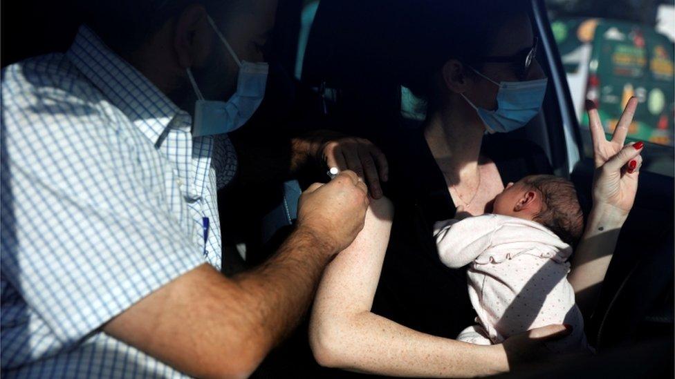 Mujer es vacunada con su bebé en brazos