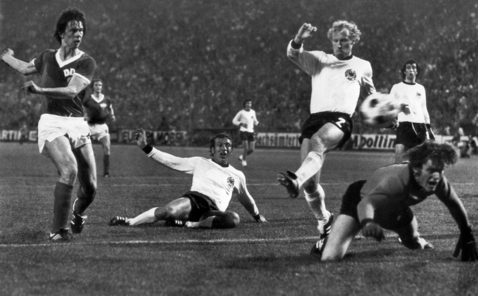 East German forward Juergen Sparwasser (L) scores the winning goal past West German defenders Horst Hoettges (C), Berti Vogts (2) and goalkeeper Sepp Maier 22 June 1974 in Hamburg during the World Cup first round soccer match between the two countries.