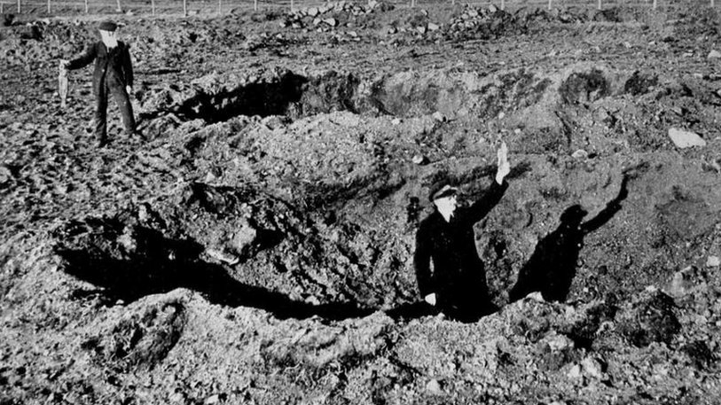 Men holding rabbit and bomb shrapnel