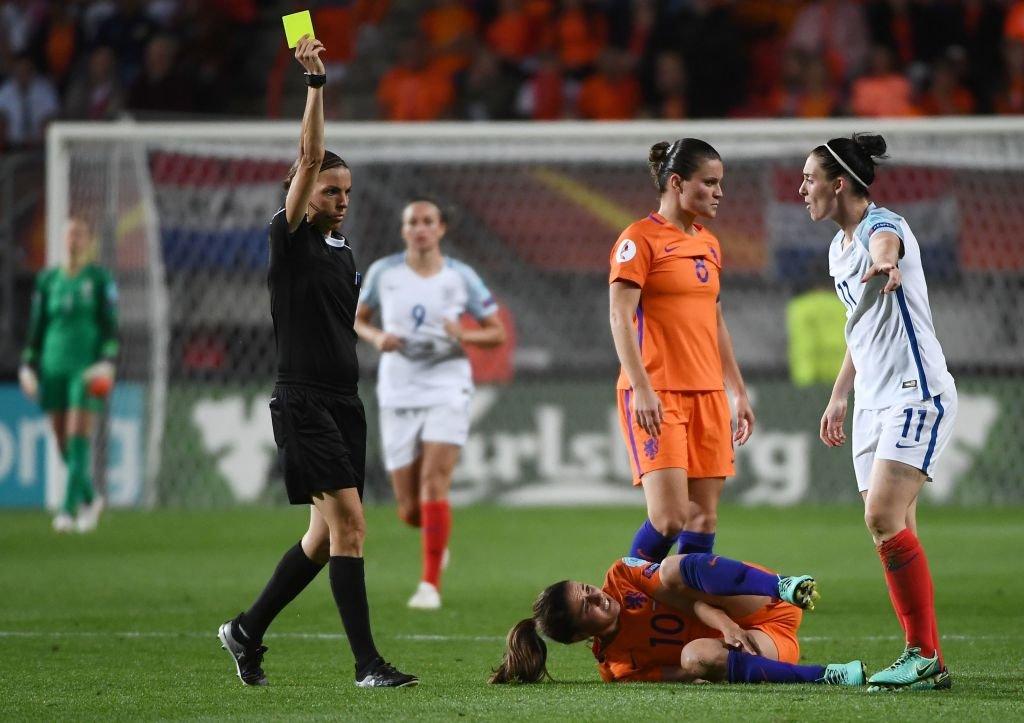 Una árbitro le muestra una tarjeta amarilla