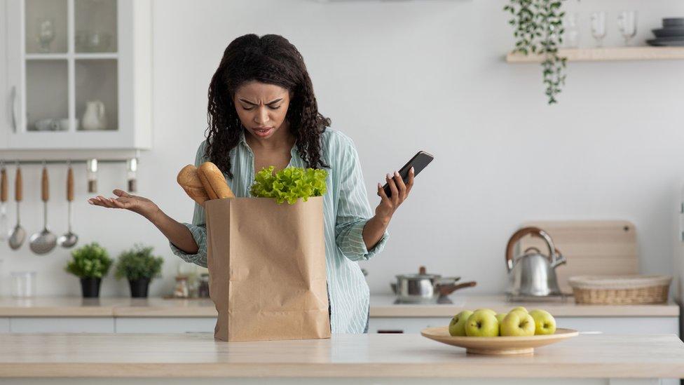 Una mujer mira desconcertada una bolsa von productos comestibles.