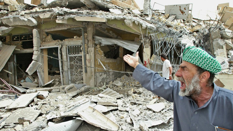 An Iraqi man reacts in front of destroyed houses in the city of Falluja on 30 April 2004