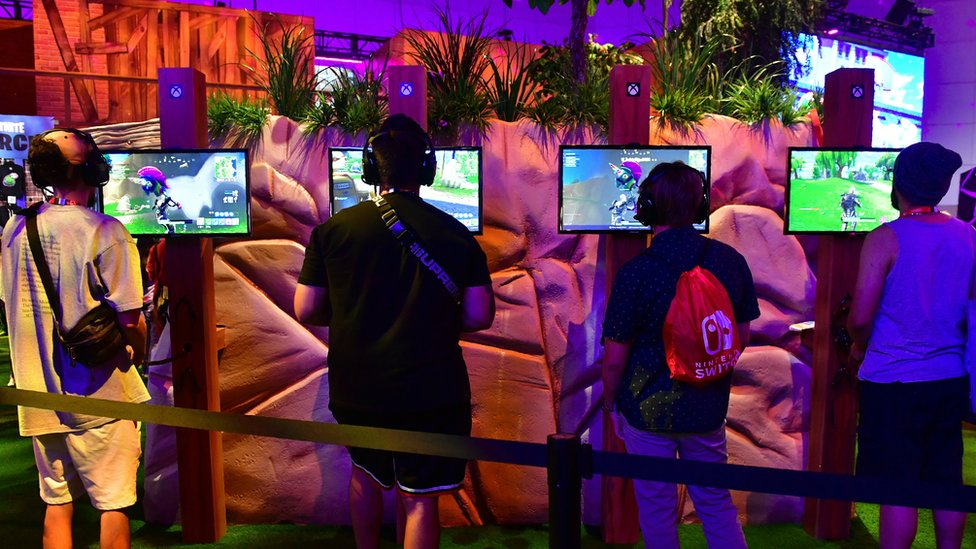 Four gamers play Fortnite on a busy stand at the E3 2018 conference in LA