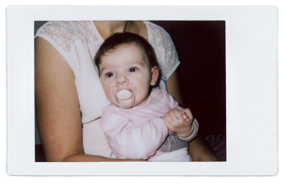 A polaroid photo of Angela with her baby