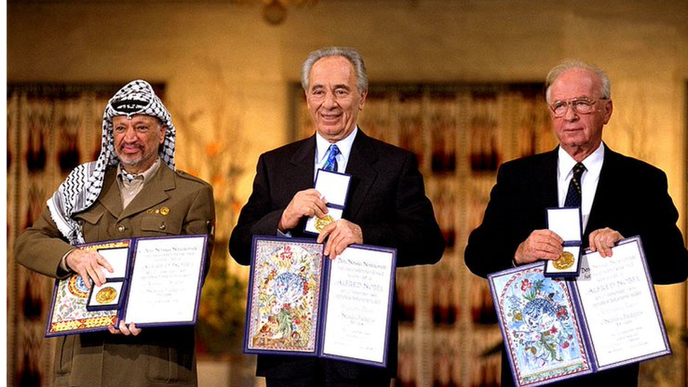 Yasser Arafat (left) poses with Israeli Prime Minister Yitzak Rabin and Israeli Foreign Minister Shimon Peres during the Nobel Peace Prize ceremony in 1994