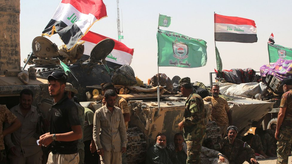 Paramilitary Popular Mobilisation force fighters gather around Tal Afar airport on 27 August 2017