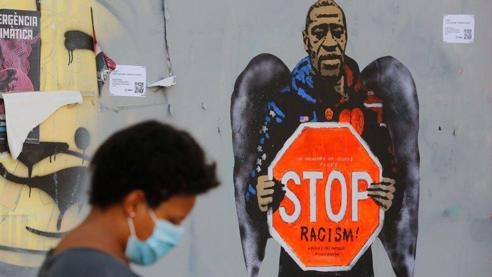 """Un grafiti con la imagen de George Floyd sosteniendo un cartel de tránsito que dice """"STOP racism"""" (detengan el racismo)."""