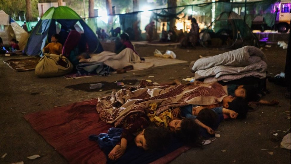 Children sleep on cloth covering hard ground in the darkness of the makeshift camp at Shahr-e-Naw Park in Kabul