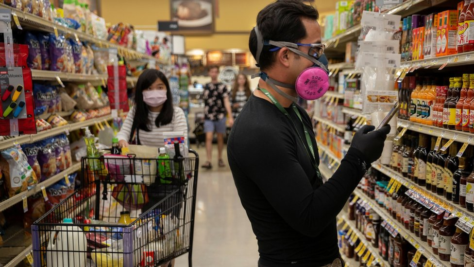 Instacart employee Eric Cohn, 34, searches for an item for a delivery order while wearing a respirator mask to help protect himself, Tucson, Arizona, 4 April 2020