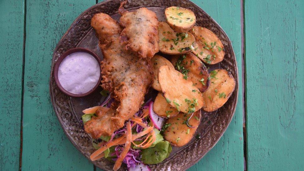 Pescado frito con papas nativas, aderezadas con una salsa a base de maqui.
