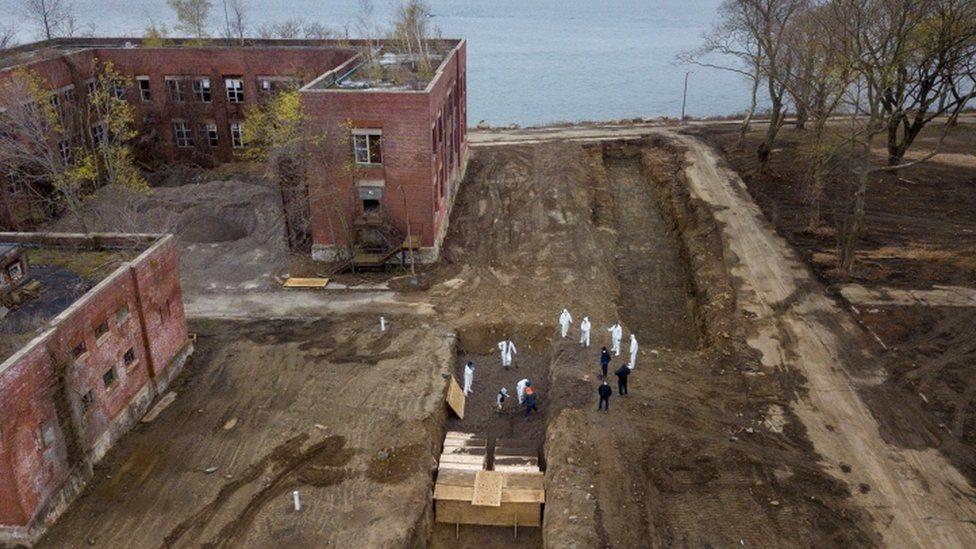 عمال يقومون بعملية دفن جماعي